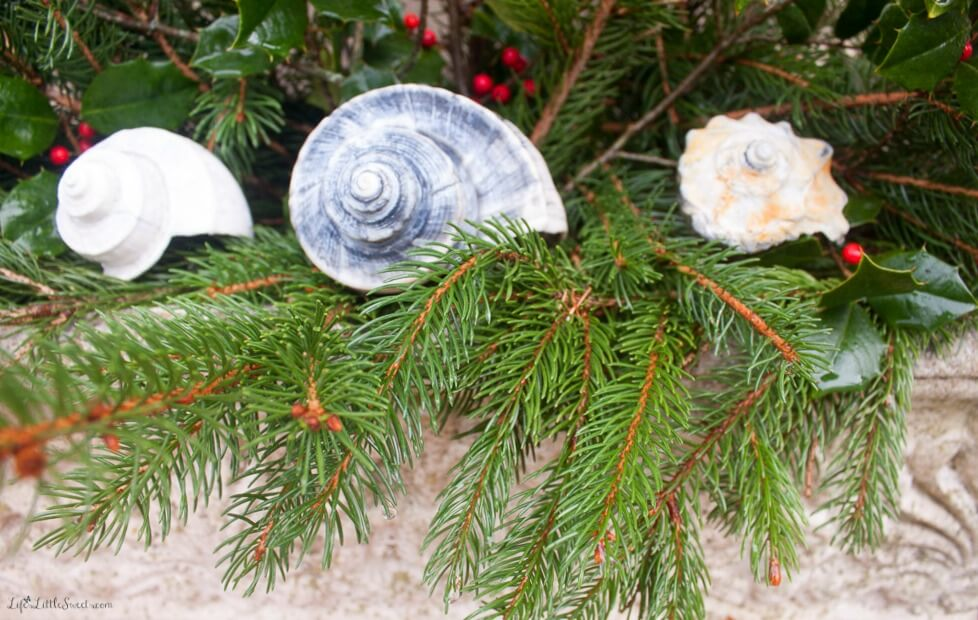Seashell Winter Planters are a great, natural way to brighten up the outdoors around your home through those long winter months! Using seashells collected over the years, pine & holly branches from around the yard - this DIY decorating idea is also budget-friendly being absolutely free! Let those sweet seashells bring reminders of the fabulous Summer to come.
