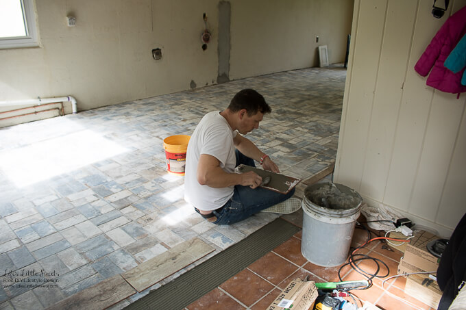 29. Eric working on the threshold with new wood printed tiles to reflect the wood beams in the ceiling | Kitchen Renovation New Tile Floor – Check out the latest from the Life's Little Sweets home kitchen renovation being our tile floor odyssey this past week (and other updates with 45 photos!)
