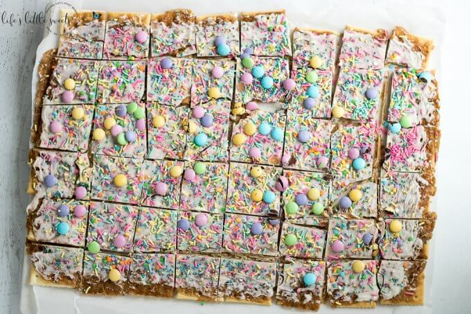 Try this Easter Saltine Toffee recipe this Spring! This classic, Saltine Toffee is an simple to make recipe, using simple pantry ingredients, white chocolate, Easter-themed, pastel sprinkles and your favorite candies. #Easter #sprinkles #candy #Saltines #whitechocolate #chocolate #candy #homemade #easy #brownsugar