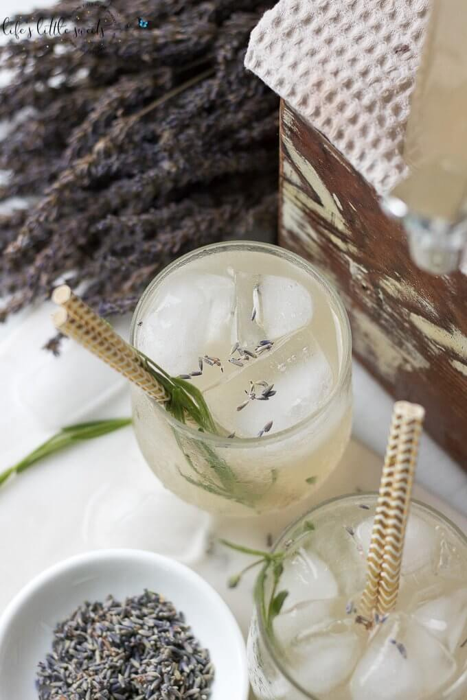 This Lavender Lemonade is made with freshly squeezed lemon juice then sweetened with a lavender-infused simple syrup. Garnish with food grade dried lavender flowers and a sprig of fresh lavender and you have yourself the ideal summer sipper! This recipe uses Lavender Simple Syrup. #lavender #lavenderlemonade #lemonade #driedlavender #iced #drink #colddrink #Summerdrink #vegan #glutenfree