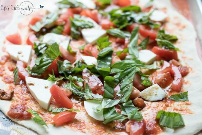 This Caprese Pizza is topped with ripe tomatoes, fresh basil, sliced mozzarella and drizzled with an olive oil-balsamic dressing. Make this homemade pizza for a bistro dinner at home! (makes 2 individual pizzas or 1 large pizza) #tomato #basil #pizza #homemade #recipe #mozzarella