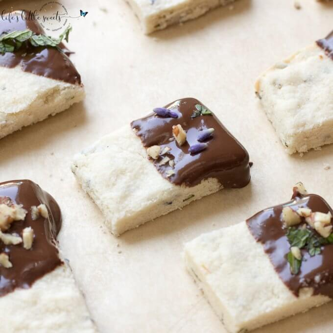 This Lavender Shortbread has fresh lavender, mint and lemon zest. Top with chopped nuts, like pecans, and dip in melted semi sweet chocolate, if you like. Welcome Summer with all it's fresh ingredients in this classic shortbread recipe. #lavender #mint #shortbread #freshlavender #lemon #lemonzest #pecans #cookies #chocolate #chocolatedipped