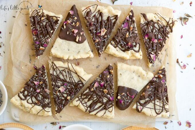 Lavender Rose Shortbread is a herb-infused, classic shortbread cookie, dipped in dark chocolate and decorated with dried lavender and rose petals. #lavender #rose #shortbread #chocolate #edibleflowers #driedflower #driedherbs #roses #cookies #recipe #homemade #butter #flour