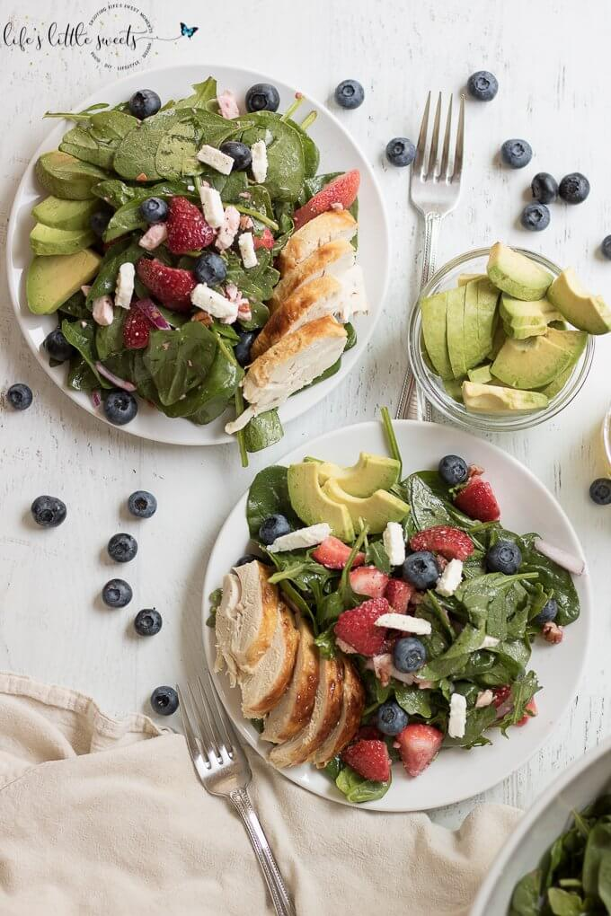 This Strawberry Salad Recipe has fresh strawberries, baby spinach, arugula, chopped pecans, feta with a light lemon vinaigrette dressing. It is garnished with blueberries, sliced ripe avocado and optional chicken. Enjoy it in the Summer months or year round! #recipe #strawberries #chicken #blueberries #avocado #feta #pecans #arugula #lemon #salad