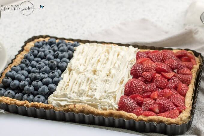 French Flag Tart has a homemade almond pie crust, a rich chocolate ganache filling, homemade, stabilized vanilla whipped cream and fresh, seasonal berries like strawberries and blueberries placed on top, in the symbol of the French Flag. #French #Frenchflagtart #tart #recipe #ganache #chocolate #espresso #coffee #berries #fruit #whippedcream #almond