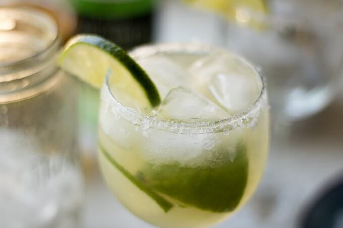 (msg 21+) This classic, Margarita recipe tastes like Summer with fresh lime juice, margarita mixer, tequila and served in a chilled glass, rimmed with Mediterranean salt crystals and lime slices. #lime #margarita #seasalt #ice #drink