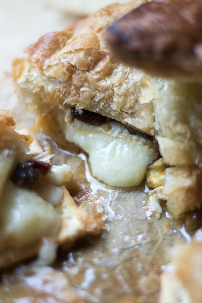 Puff Pastry Baked Brie is an easy recipe with fruit, nuts and jam all wrapped in flaky puff pastry and baked until it is hot and gooey. It tastes great served with your favorite crackers or bread. Make this simple yet satisfying appetizer recipe for your next gathering! #cheese #brie #puffpastry #appetizer #cranberries #Autumn #food #Fall #recipe #nuts #pistachios