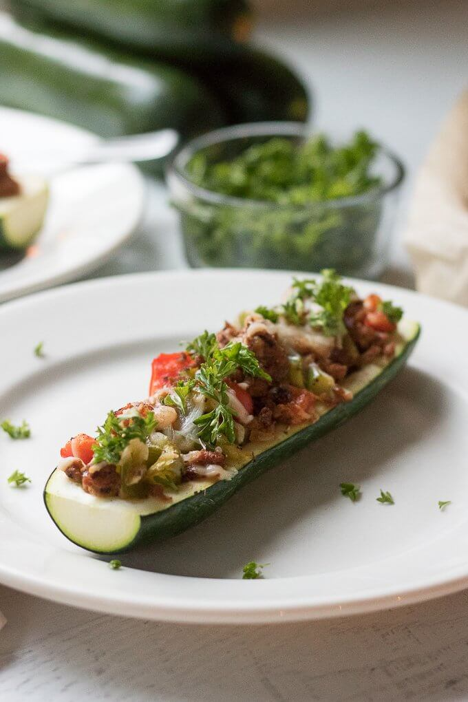 These Stuffed Zucchini Boats are a savory, delicious and complete dinner allowing you to get your dose of vegetables. Filled with your favorite meat, in this case, lean ground turkey, they also have bell peppers, onions and grated cheese. This low-carb dinner is a great way to use up all that garden zucchini! #zucchini #zucchiniboats #squash #turkey #cheese #parsley #onions #peppers