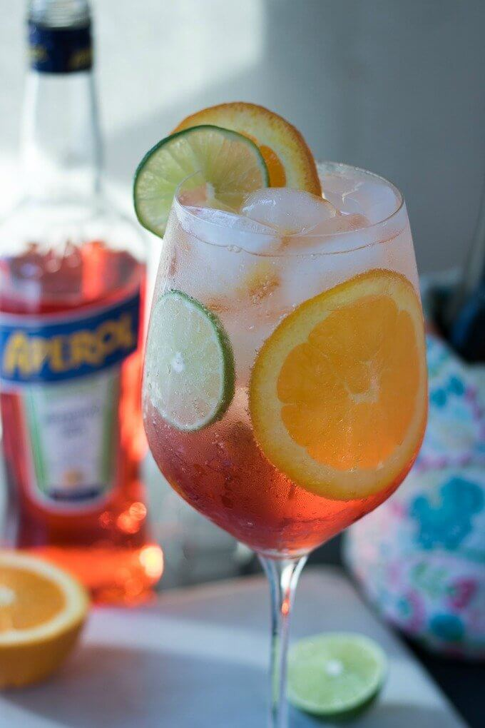 The Aperol Spritz is making a comeback for a reason! This Italian classic cocktail consists of Aperol, Proscecco, orange and lime slices, and club soda. Perfect for dinner parties or happy hour, the vibrant color and flavors add to the joy of any occasion! #ad @sofabfood #sofabfood