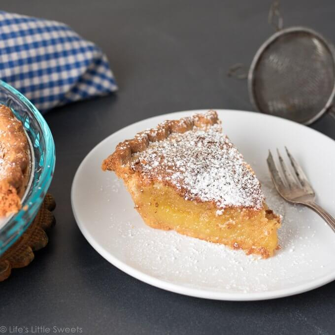 This Chess Pie recipe is a simple, solid, sweet pie recipe topped with confectioner's sugar, a sprinkling of crushed sea salt. It has a distinctive yellow batter which is thickened with corn meal. Bring to a holiday gathering, potluck or make it for an easy dessert after a weeknight meal. Serve it cold or warm and enjoy this delicious pie with a hot cup of coffee! (makes 1, 9-inch pie) #pie #chesspie #dessert #sweet #sugar #cornmeal #confectionerssugar