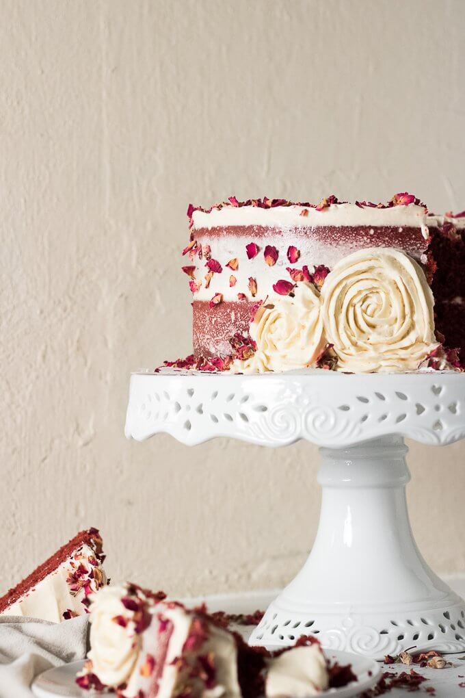 This Red Velvet Cake Recipe is a tall, dramatic, 2-tiered cake recipe that uses red cocoa, espresso powder, and is topped with a delicious cream cheese frosting. This cake is festive, attractive and perfect for year-round celebrations, birthdays and gatherings! #redvelvet #cake #recipe #creamcheese #frosting #roses #rosecake #nakedcake