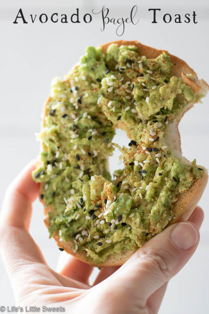 This Avocado Bagel Toast makes the perfect, satisfying and savory breakfast to start the day or mid-day snack. It has mashed, ripe, fresh, avocado, tuxedo sesame seeds, kosher salt, fresh ground peppercorn medley and smoked paprika sprinkled on top. #avocado #avocadobageltoast #avocadotoast #recipe #smokedpaprika #sesameseeds #salt #pepper