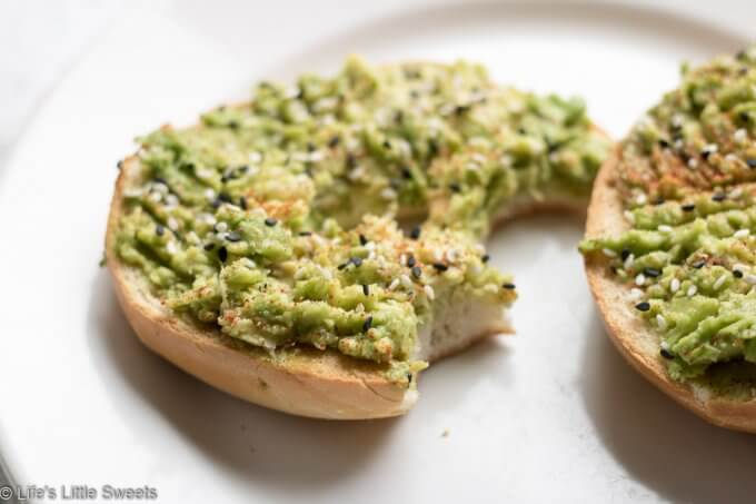 This Avocado Bagel Toast makes the perfect, satisfying and savory breakfast to start the day or mid-day snack. It has mashed, ripe, fresh, avocado, tuxedo sesame seeds, kosher salt, fresh ground peppercorn medley and smoked paprika sprinkled on top. #avocadobageltoast #breakfasts #snacks #recipe #sesameseeds #tuxedosesameseeds #smokedpaprika #koshersalt #salt #savory