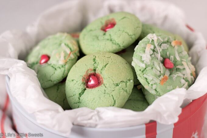 Grinch Sugar Cookies are classic sugar cookies, tinted green with a red candy heart in the middle. These delicious cookies are inspired by the beloved children's book and movies, The Grinch. enjoy these easy, fun, homemade, cookies during the holidays or throughout the year!  #grinchcookies #cookies #thegrinch #grinchfood #dessert #sweets #thegrinchmovie #sugarcookies #grinchsugarcookies