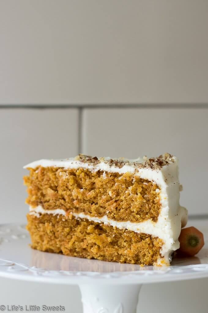Homemade Classic Carrot Cake with Cream Cheese Frosting has cinnamon, vanilla and 3 cups of finely shredded carrots throughout this delicious cake. It is a 2-tiered cake with smooth and sweet homemade cream cheese frosting. It's topped with optional chopped pecans and decorated with fresh, peeled little carrots. #carrotcake #Eastercake #Easterfood #carrot #carrots #dessert #pecans #sweet