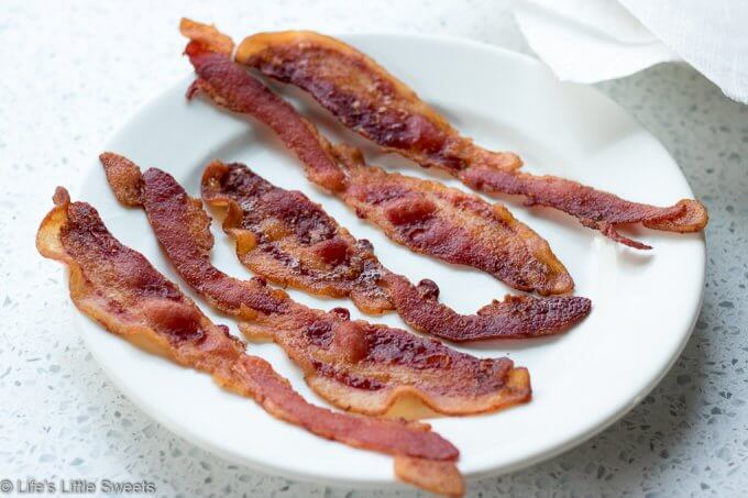 Oven Baked Bacon is savory, crispy and easy way to make a large amount of bacon right in your oven. This way of making bacon frees up your stove top and is great for making a big breakfast, brunch or if you need a large amount for a recipe. #paleo #glutenfree #keto #bacon #baked #ovenbaked #savory #breakfast #brunch #pork