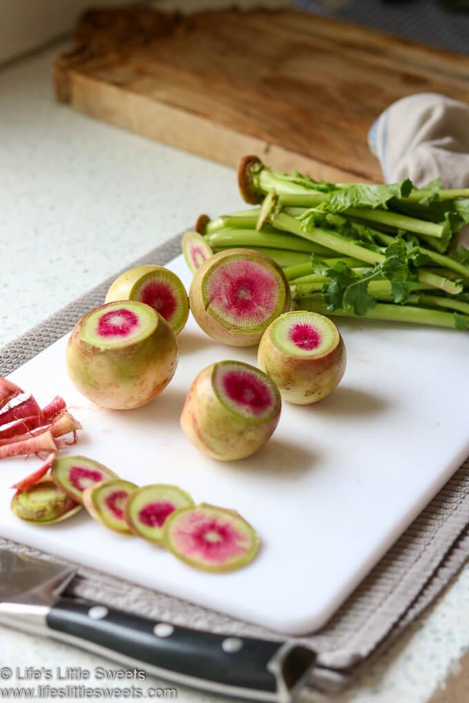 Watermelon Radish on a cutting board, tops and tails cut