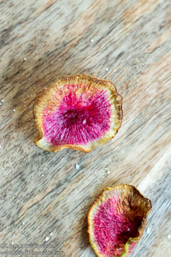 2 watermelon radish chips on a wood board with salt