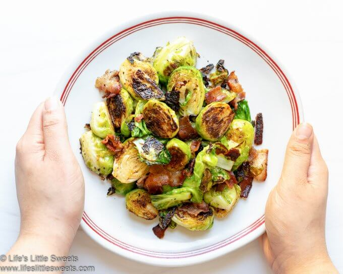 Pan-Fried Bacon Brussels Sprouts on a white plate with red stripes and white background