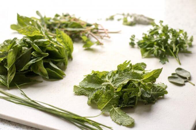 green herbs on a white cutting board